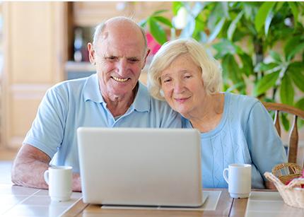 casal de idosos com roupas em tons de azul, sentados, sorrindo em frente ao notebook